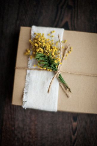 A small bouquet of yellow flowers on burlap and secured by twine make excellent ...