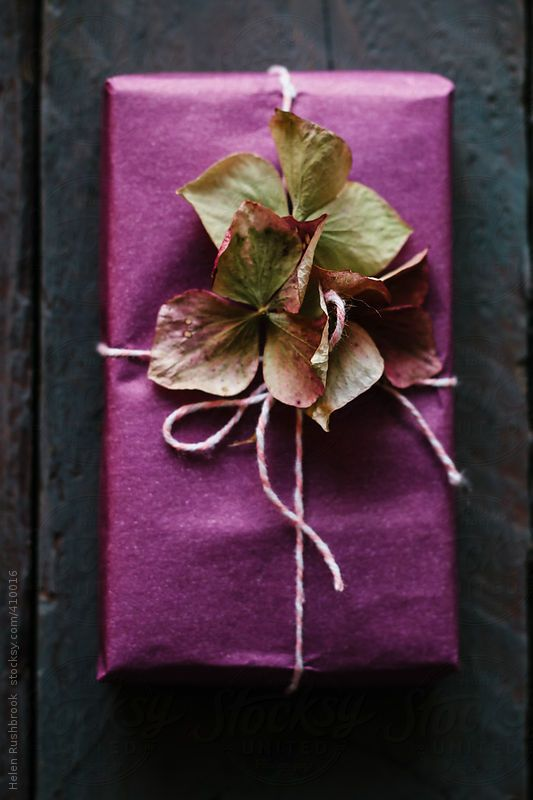 Purple paper and decorated with dried flowers.