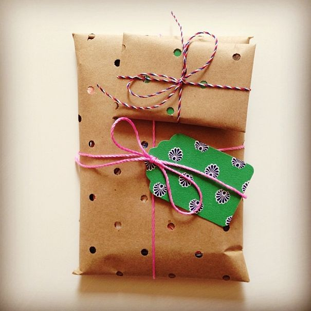 Punch holes in brown gift wrapping paper.