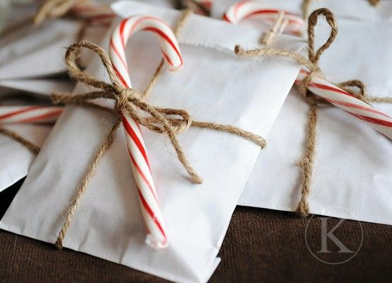 white paper bags with jute twine and a candy cane topper