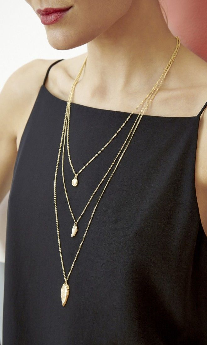 Three-tiered, delicate necklace with dainty charms in matte gold-toned metal. In...