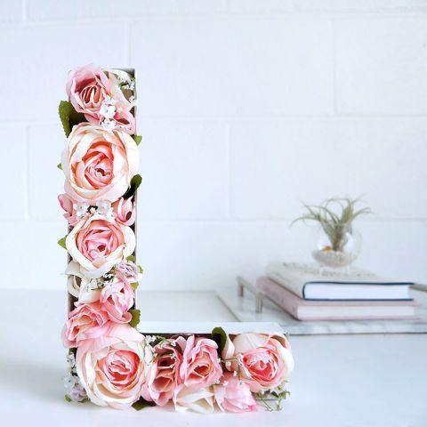 Hot-glue faux flowers inside a hollow papier-mâché letter for a personalized g...